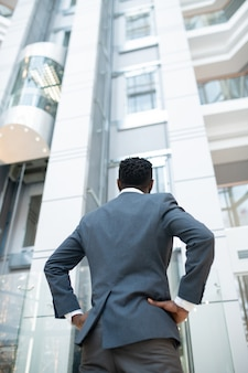Rear view of black man in jacket standing with hands on hips in modern business center