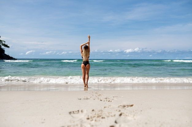 Вид сзади: блондинка, красивая девушка позирует на пляже и поднимая руки вверх. тропический отдых. путешествие в жаркие страны