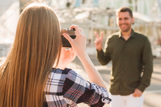 Rear view of blonde hair woman taking picture of man with peace gesture