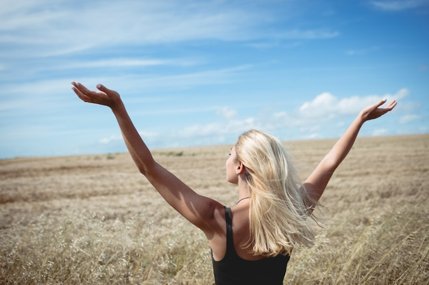 Rear view of blonde woman standing in field
