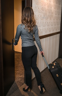 Rear view of a blonde young woman with suitcase entering the hotel room