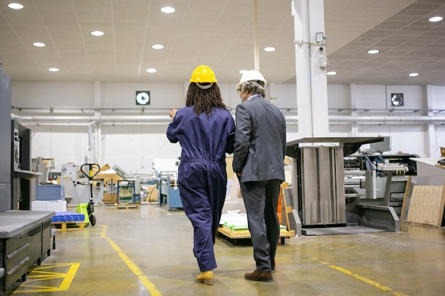 Rear view of boss standing at factory and listening plant worker