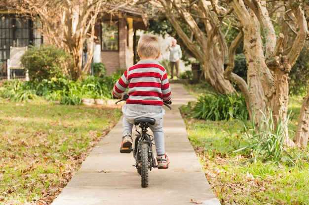 Rear view of boy cycling in front yard