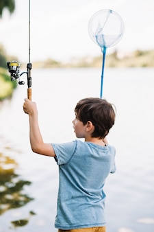 Rear view of boy raising hands holding fishing rod and net in front of lake
