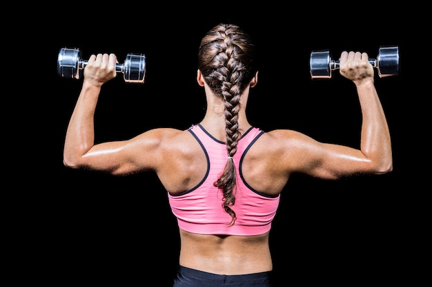 Rear view of braided hair woman exercising dumbbells against black background