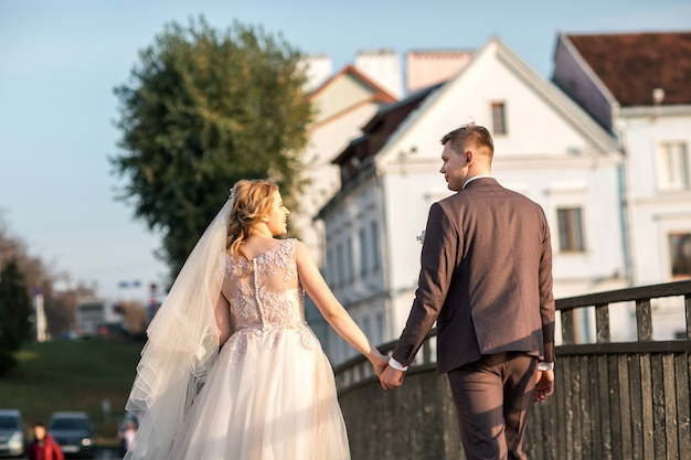 Вид сзади. жених и невеста идут по улице города. фото с копией пространства