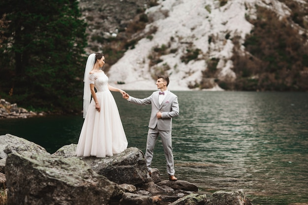 Rear view of bride and groom, standing on the lake shore with scenic mountain view in poland, morskie oko