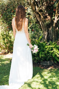Rear view of a bride holding flower bouquet in hand standing in the park