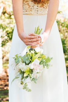 Rear view of a bride with hand behind her back holding flower bouquet