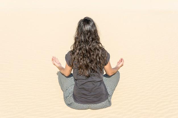 Rear view of brunette woman doing yoga in a dune in fuerteventura.