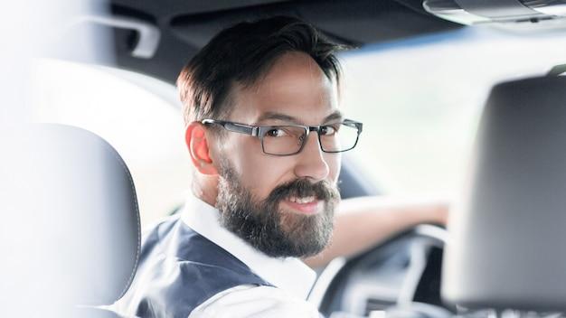 背面図。車のハンドルの後ろに座っているビジネスマン。輸送と人々