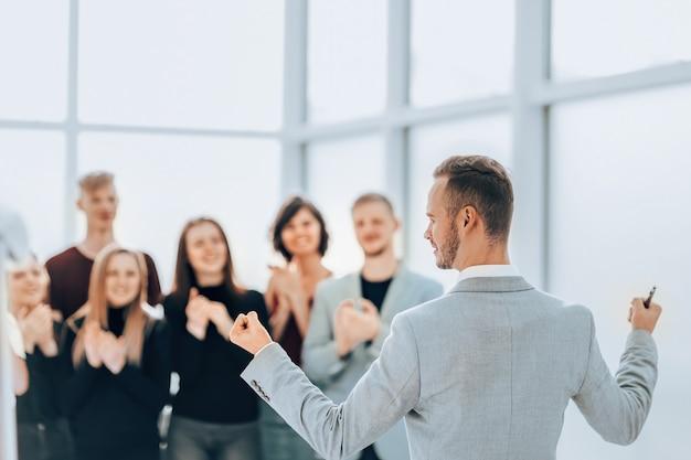 背面図。拍手するビジネスチームの前に立っているビジネスマン
