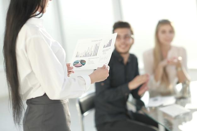 배면도. 회의실에 재정 일정이 서 있는 비즈니스 여성. 비즈니스 개념