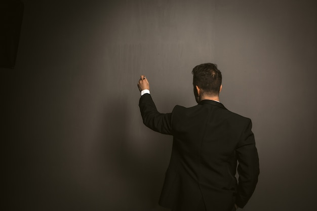 Rear view of businessman in a black suit writes something on dark gray wall.