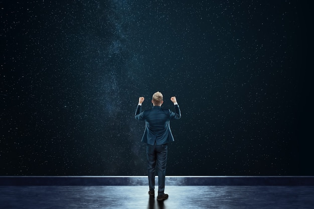 Rear view businessman stands against the background of the starry sky