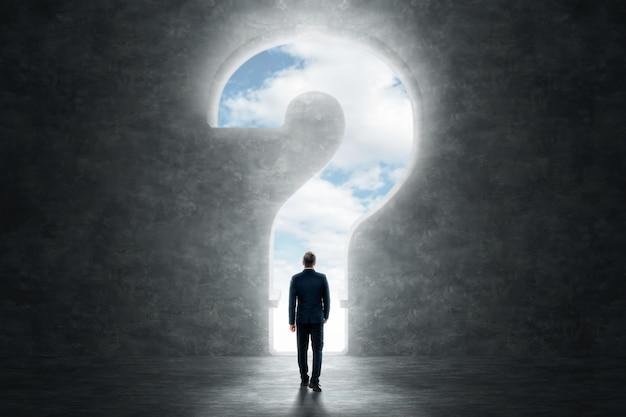 背面図のビジネスマンは、大きな疑問符の背景に立っています。
