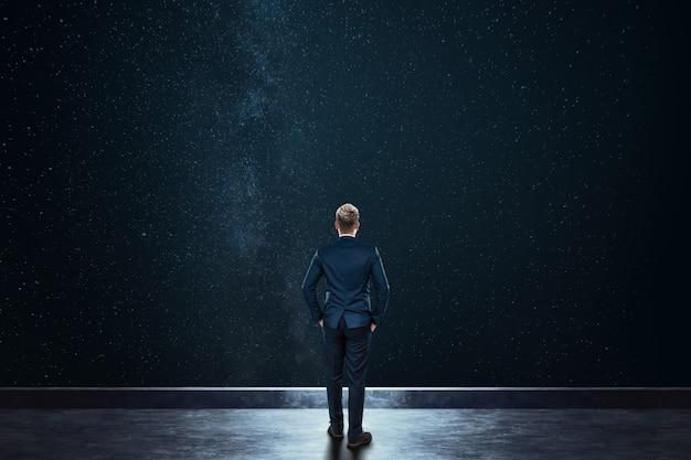 背面図のビジネスマンは星空を背景に立っています