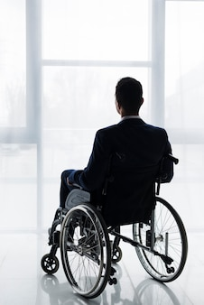 Rear view of a businessman in suit sitting on wheelchair looking at window