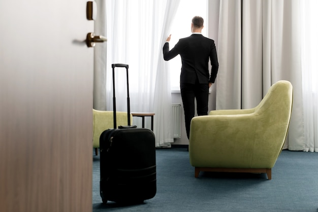 Rear view of businessman wearing dark suit standing in hotel room looking into window