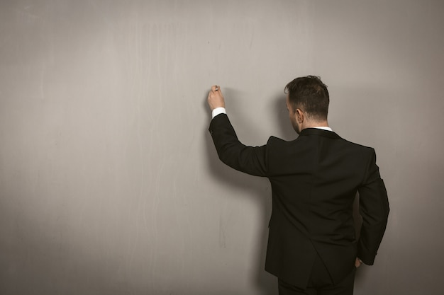 Rear view of businessman writing on wall. creative man in black elegance suit drawing by pan or chalk on light grey wall. template concept. toned image