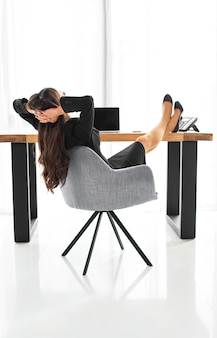 Rear view of a businesswoman sitting on chair relaxing at office desk
