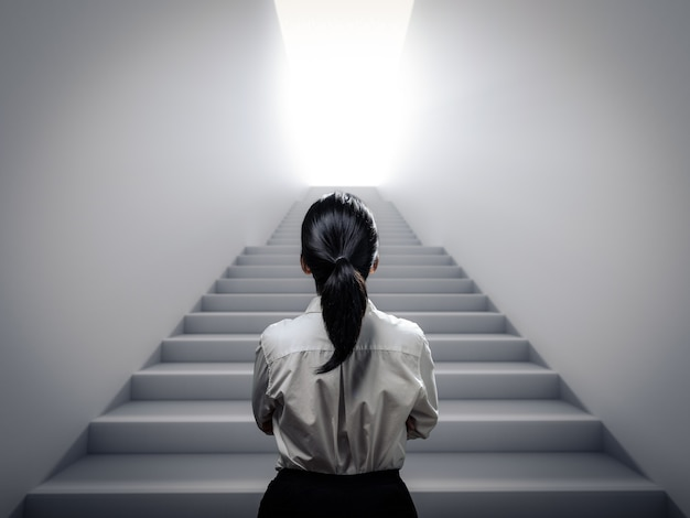 Деловая женщина, вид сзади, стоя на лестнице