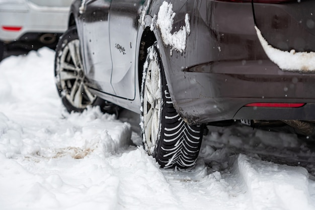 Rear view of car with winter tyres in snowy road, close-up