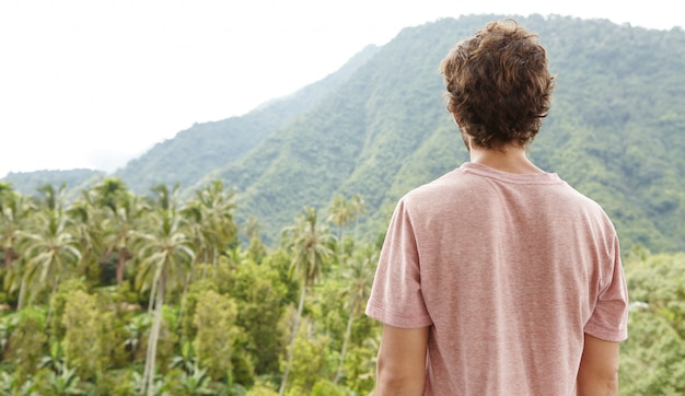 Rear view of caucasian man in t-shirt standing outdoors in front of rainforest and contemplating beauties of exotic wild nature on sunny day. tourist enjoying beautiful landscape during trekking trip