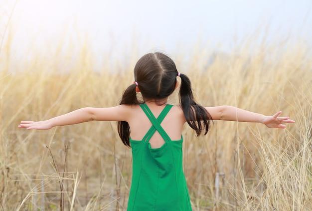 후면보기 자식 소녀는 그녀의 손을 열어 초원 필드에서 이완.