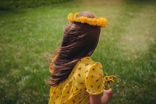 彼女の頭にタンポポの花輪を持って風に流れる女の子の長い髪の背面図のクローズアップ...