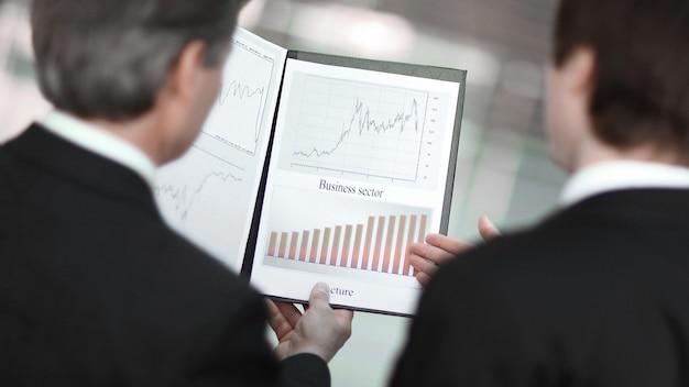 Вид сзади. крупный план деловых партнеров, обсуждающих финансовые документы. бизнес-концепция