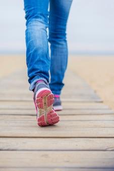 ビーチの上を歩く女性の後姿のクローズアップ