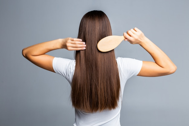 Rear view of combing healthy long straight female hair isolated on gray