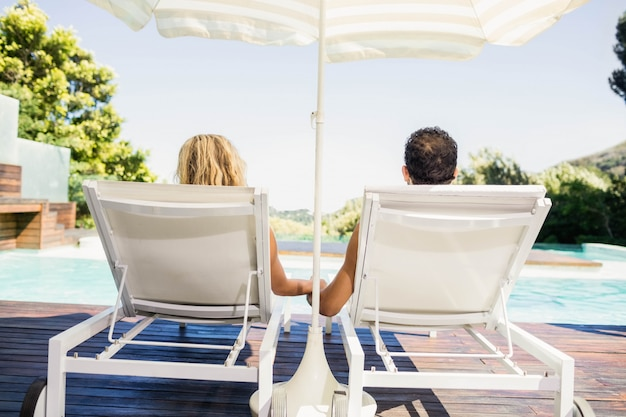 Rear view of couple on deck chairs poolside