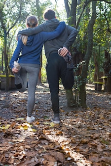 Rear view of couple doing warm-ups together