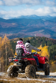Rear view of couple driving a quad bike atv at the hill