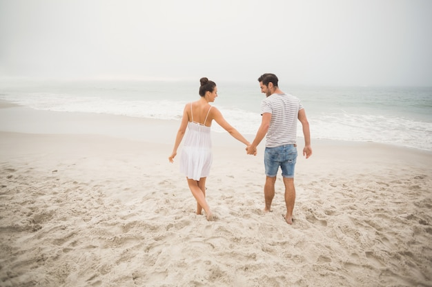 Rear view of couple holding hands and walking on the beach