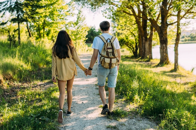 Rear view of couple holding hands walking on footpath
