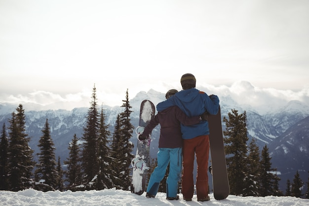 Rear view of couple holding snowboard at mountain during winter against sky