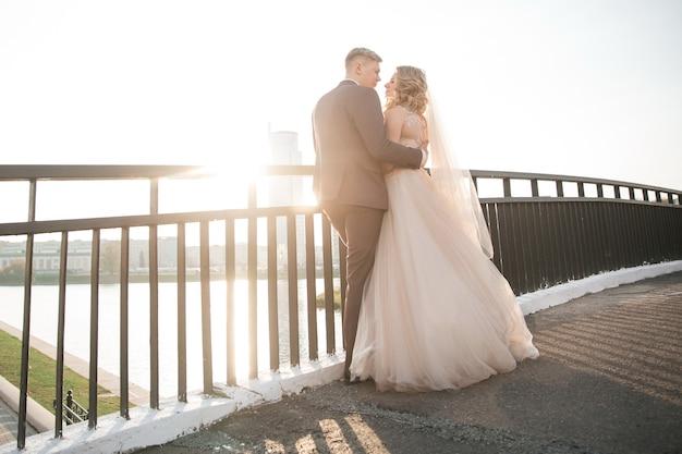 Вид сзади. пара молодоженов, стоящих на мосту. фото с копией пространства