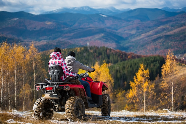 Rear view of couple on a quad bike atv at the hill