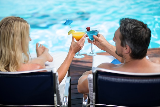 Rear view of couple toasting martini glass while relaxing on sun lounger