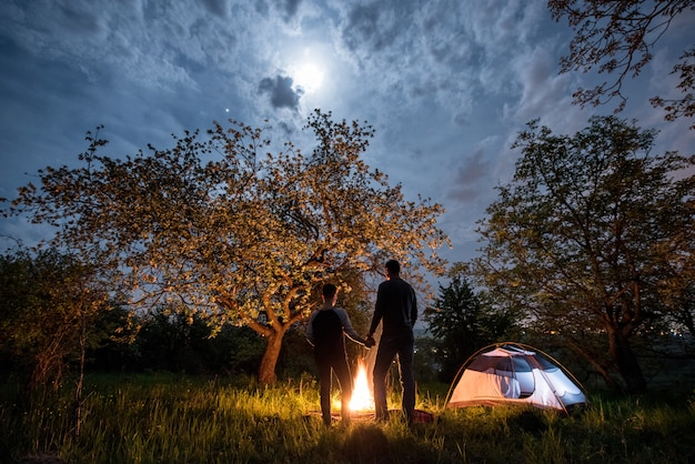 Rear view of couple tourists standing at a campfire, holding hands near tent under trees and night sky with the moon