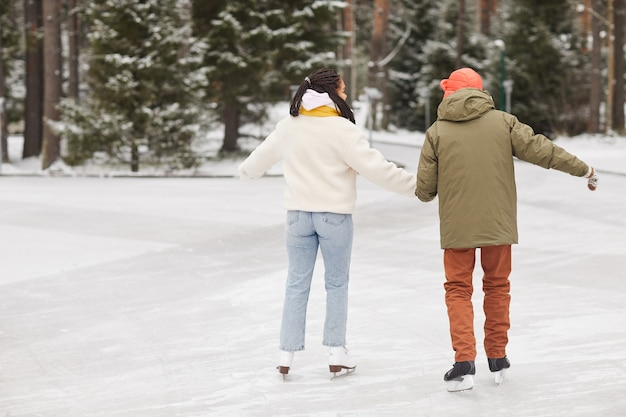 Rear view of couple in warm clothing skating together on skating rink in winter