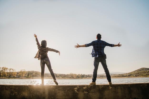 Vista posteriore di coppia con le braccia aperte alzando lo sguardo al cielo