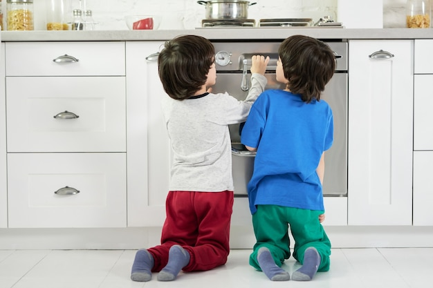 Rear view of curious little hispanic boys, twins watching cake baking in the oven, crouching down in the kitchen. children, cooking concept