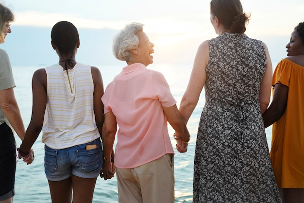 Rear view of diverse senior women holding hands together