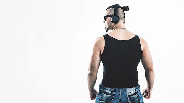 背面図-dj-明るい壁にヘッドフォンを備えたスタイリッシュな髪型のラッパー。写真にはテキスト用の空きスペースがあります