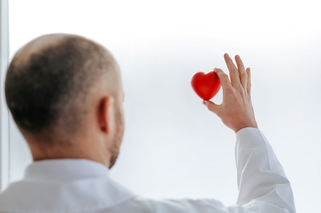Rear view. doctor looks at the small red heart in his hands. the concept of health protection.