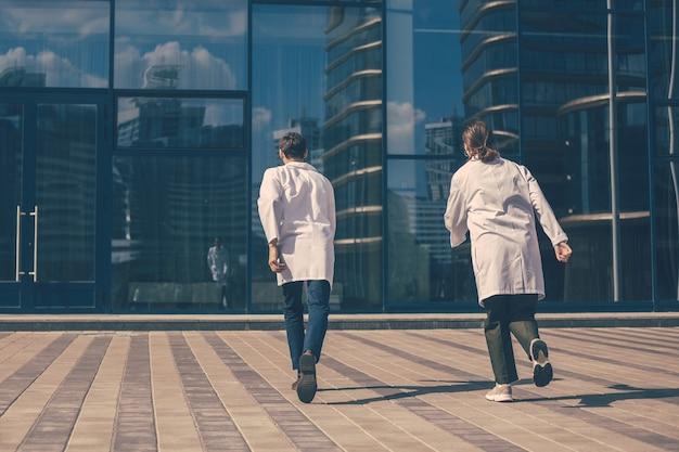 Вид сзади. врачи бегут оказывать первую помощь. фото с копировальным пространством.